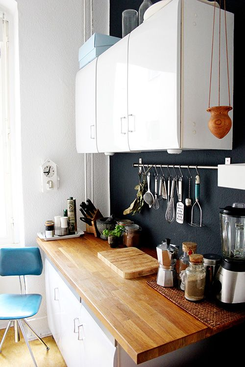 a cozy small white kitchen with a light-colored countertop and a chalkboard backsplash that adds style