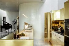 01 The kitchen has a strong wow factor, it's done with brass, marble and concrete, it shines from a distance