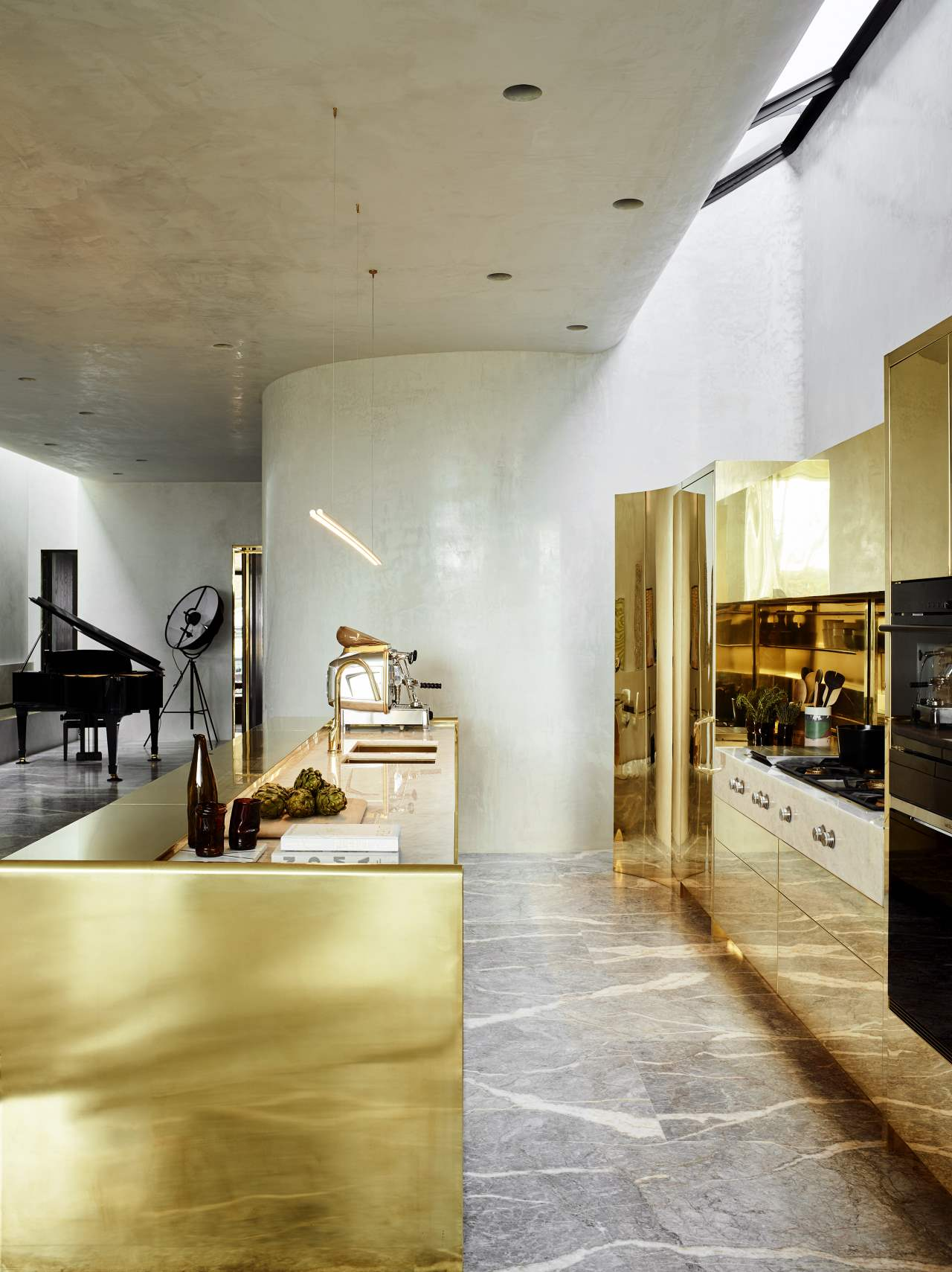 The kitchen has a strong wow factor, it's done with brass, marble and concrete, it shines from a distance