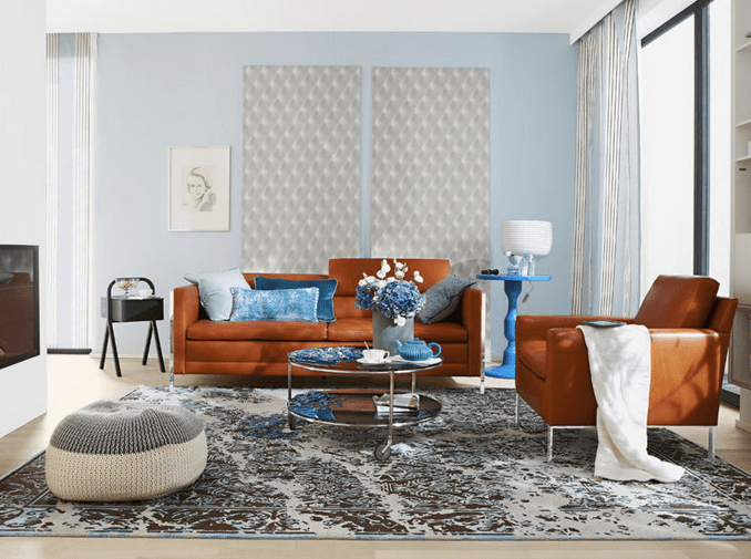 The living room is done with rust colored leather furniture and blue accents