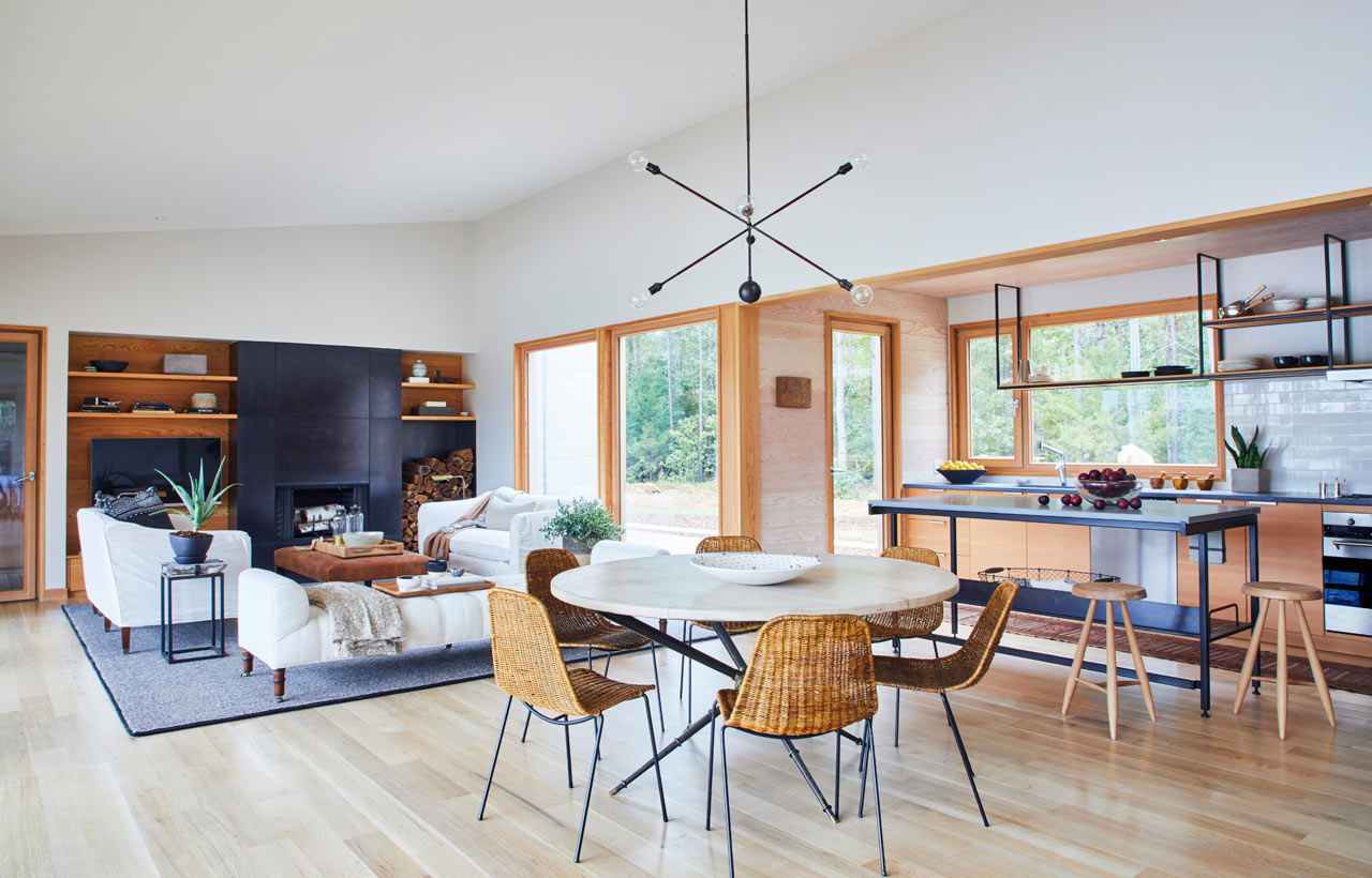 The main space consists of a living, dining room and a kitchen in one, with many windows and wicker touches