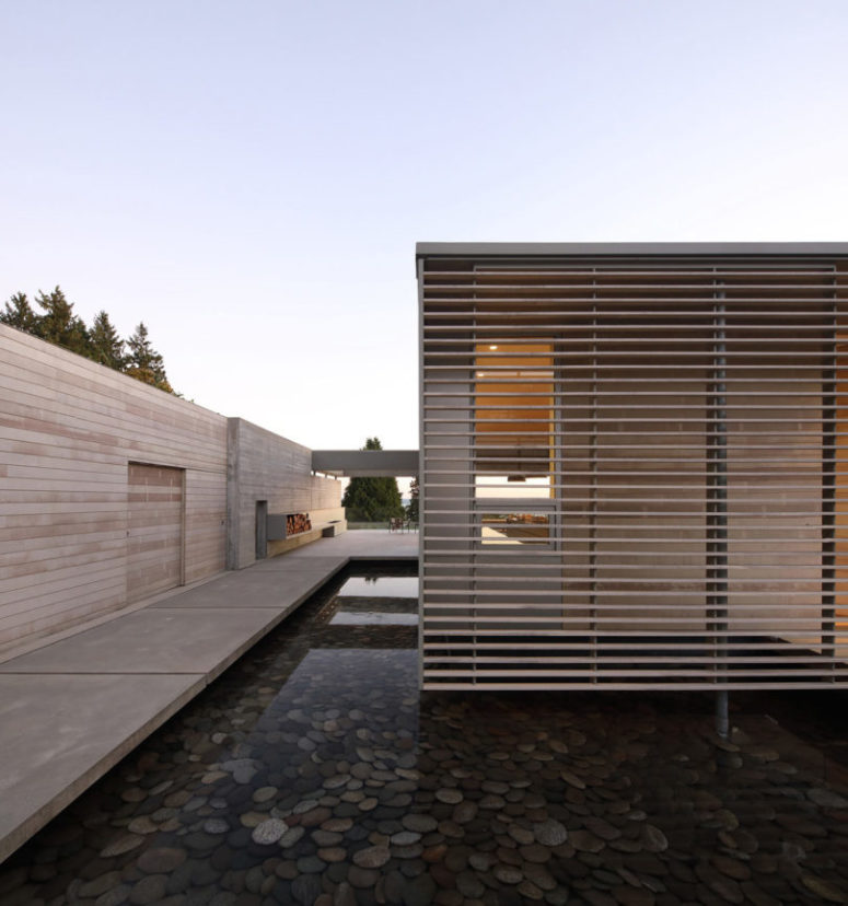 Thanks to the clever design over the pond with pebbles the house seems to be floating over it