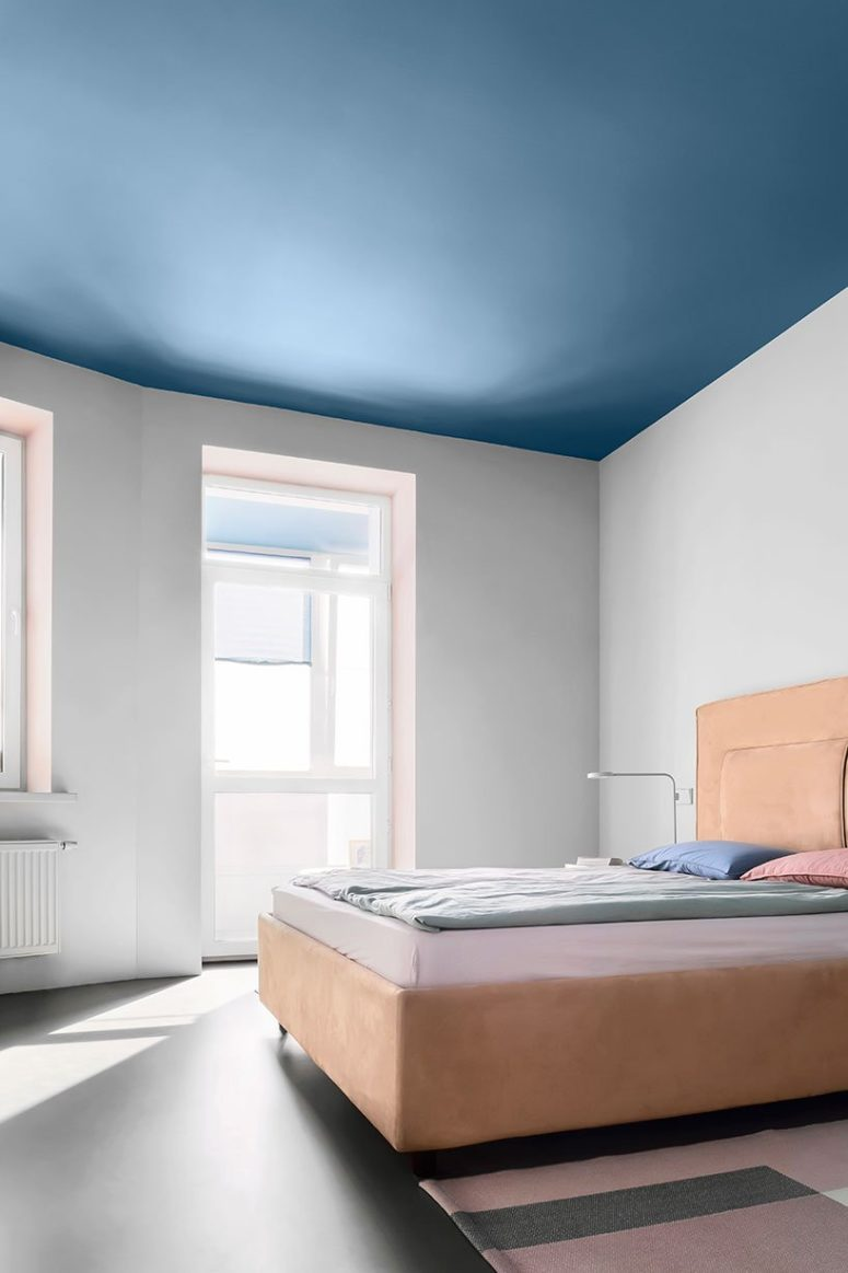 The bedroom is done with a blue ceiling, a peachy pink upholstered bed, sconces and a large window to fill it wiht light