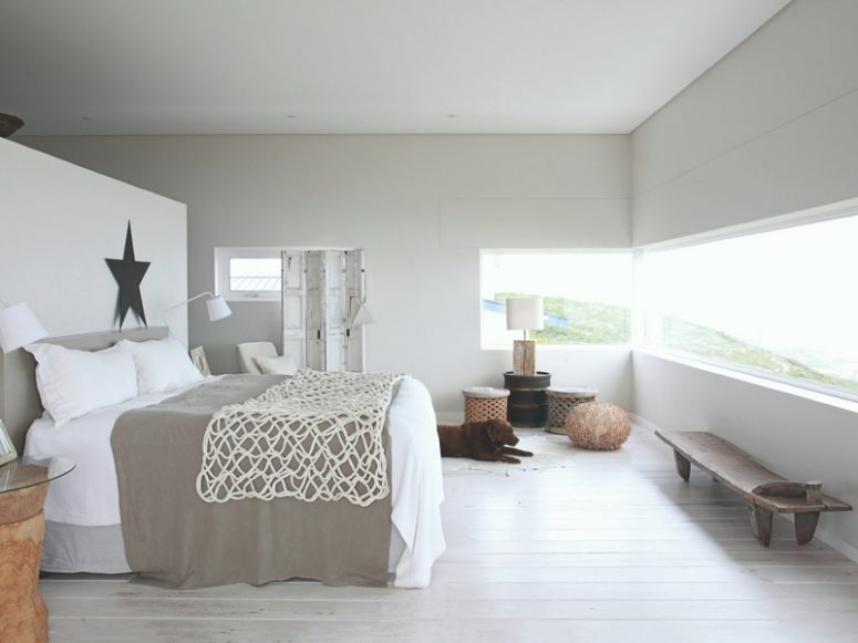 The master bedroom is done in white and light grey, with a cool long window, soft textiles and wood and wicker for a ship feel