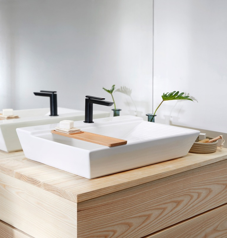 The washbasin has a geometric shape, a black matte tap and a little wooden tray