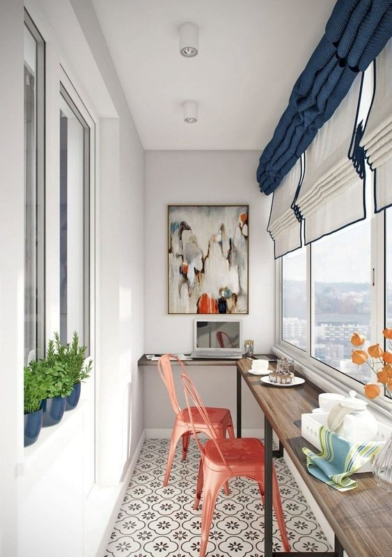 a balcony breakfast bar with a windowsill and a couple of coral painted metal chairs