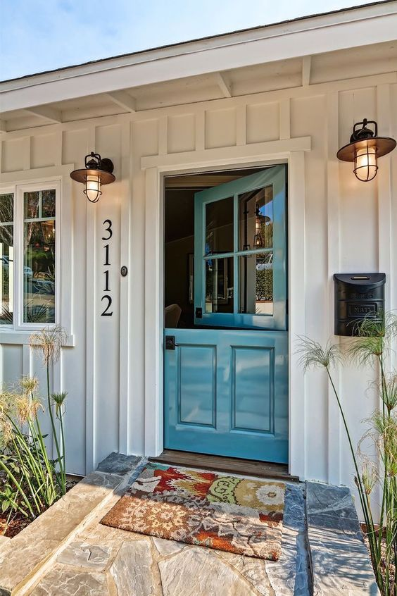 a beach cottage entrance with a beautiful blue Dutch door and cute lamps