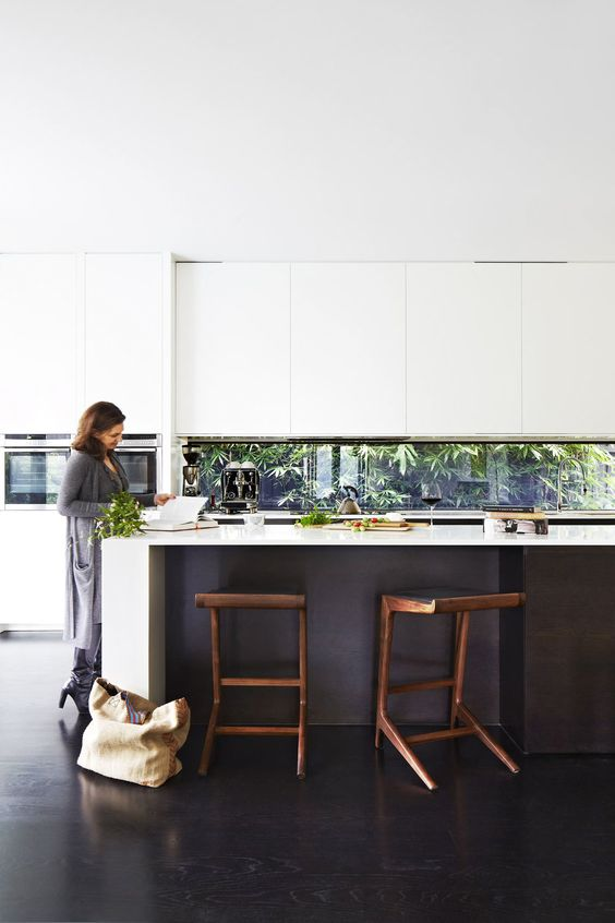 a black and white kitchen is made fresh with a window backsplash that shows off greenery