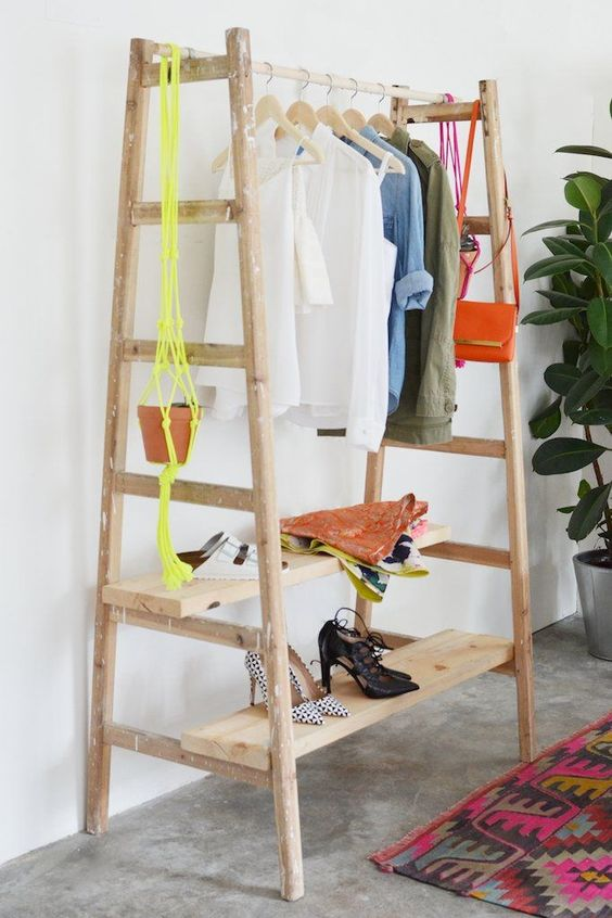 a comfy clothes and shoe rack made of a couple of ladders and some wooden planks, easy to DIY and very functional