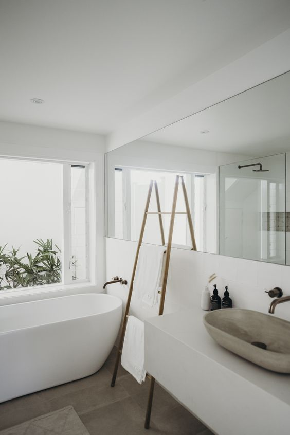 a minimalist white bathroom with a long mirror, a free-standing bathtub, a stone sink and a ladder for storage