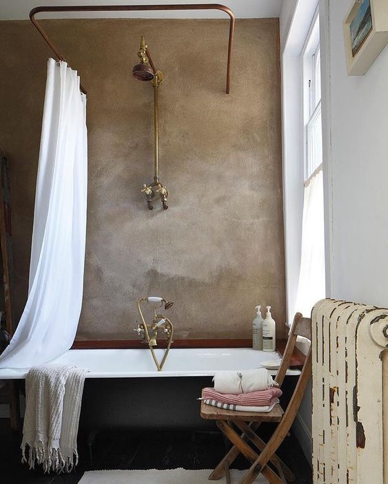 a taupe plaster wall in the bathroom makes a stylish statement and metallic touches add a vintage feel