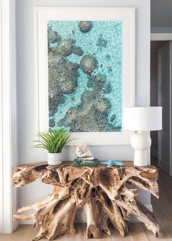 a unique raw edge wood console, a turquoise star fish and an oversized photo from a holiday for a wow effect