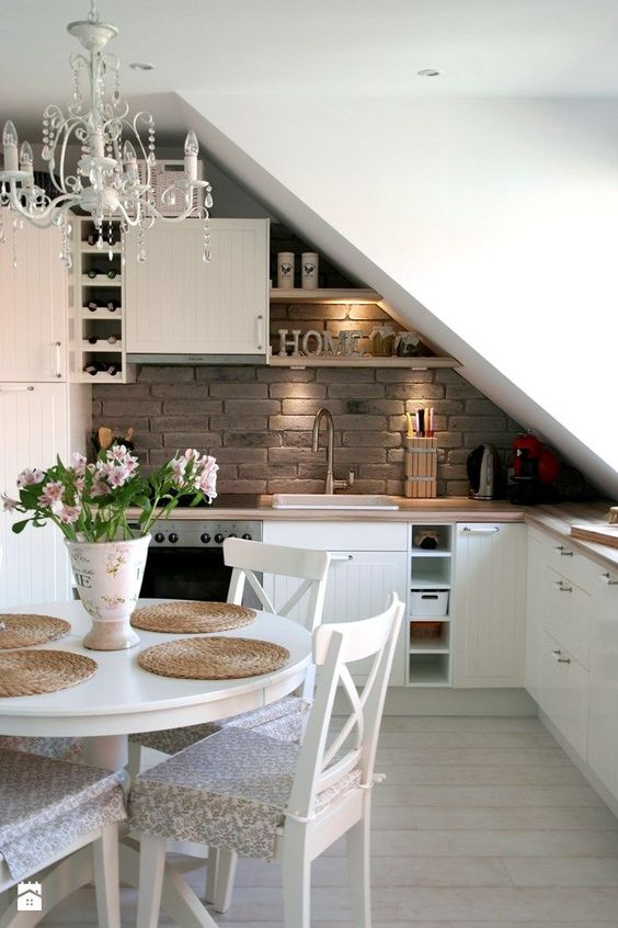 an attic kitchen with the ceiling over the sink and cooker, shelves that fit the angle