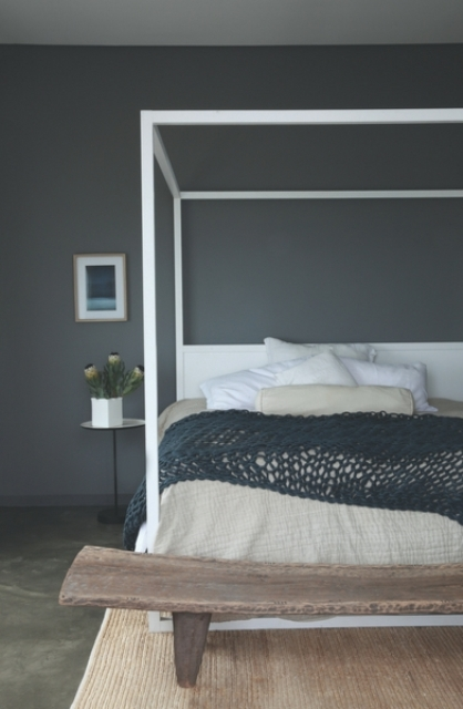 A guest bedroom is done with a graphite grey statement wall, a wooden bench and a framed bed plus textiles