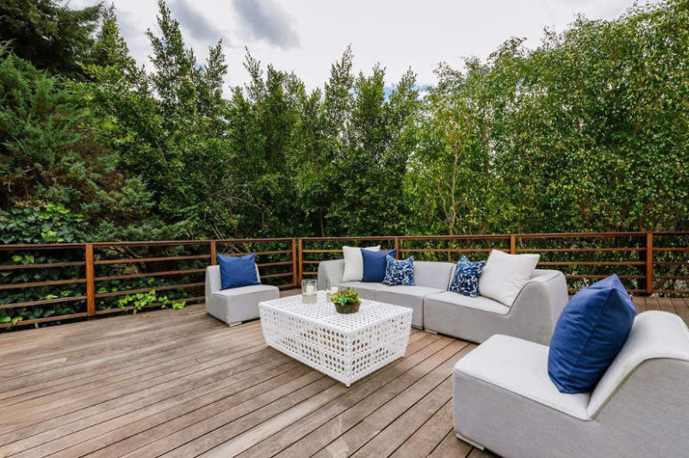 The deck features comfy upholstered furniture and there's lush greenery all arond the space