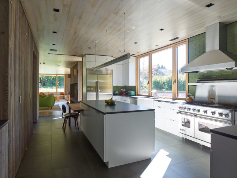 The kitchen is done with white cabinets, there's a large window that lets the views