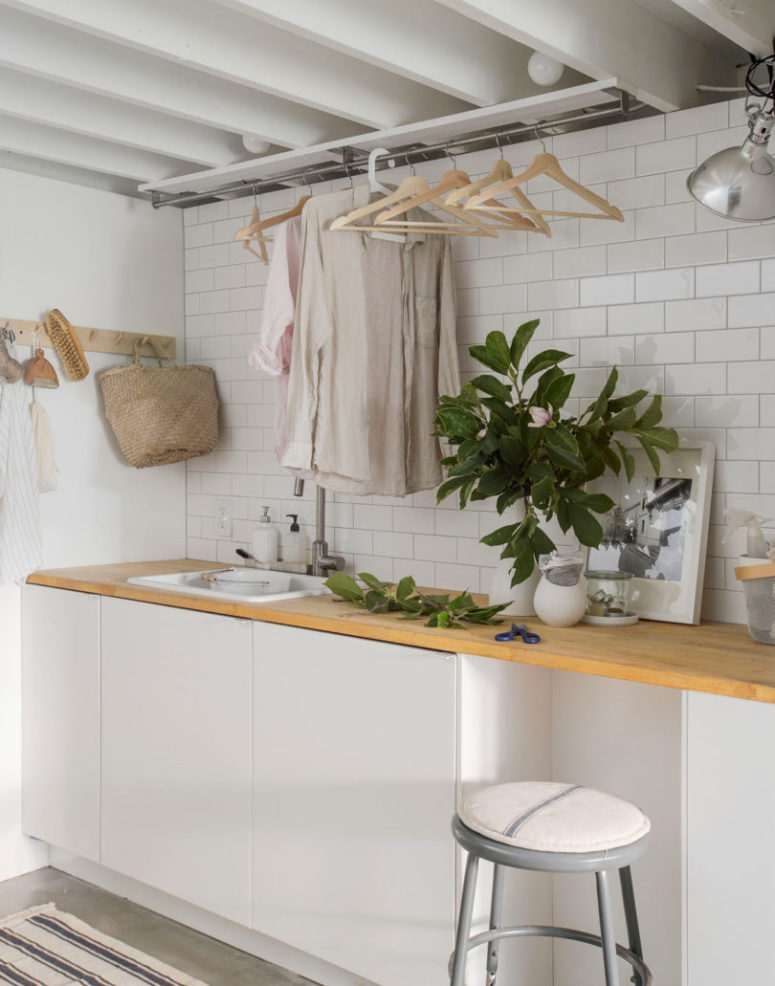 There's a laundry room with white tiles, cabinets, wooden countertops and some comfy clothes storage