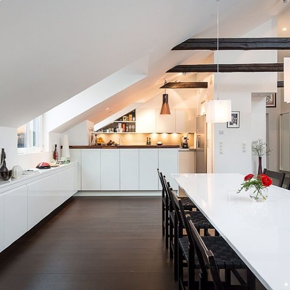 a contemporary attic kitchen in white with some dark touches and cabinets that fit the angle