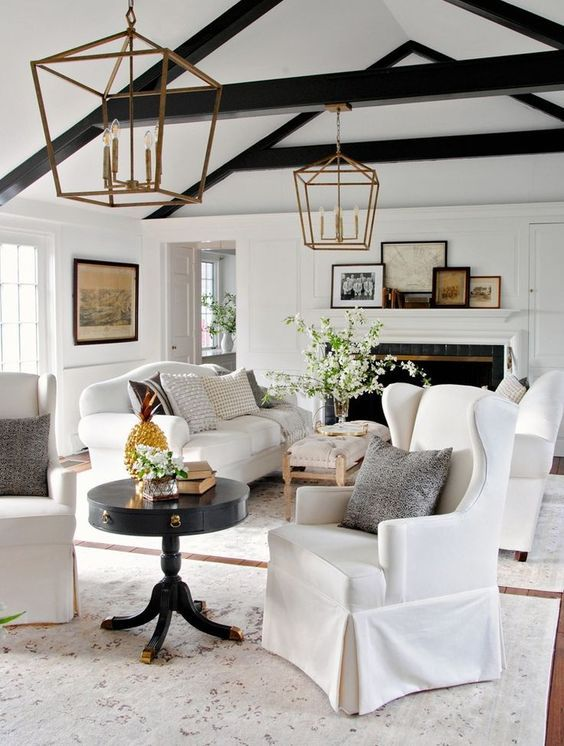 a fresh take on a farmhouse interior with two white sofas and black wooden beams for a contrast