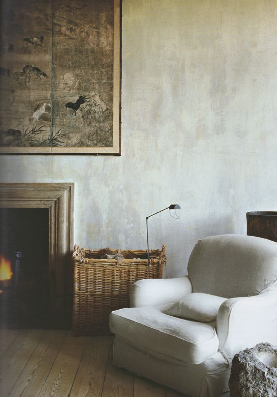 a neutral cozy space with greyish plaster walls that add more texture to the space