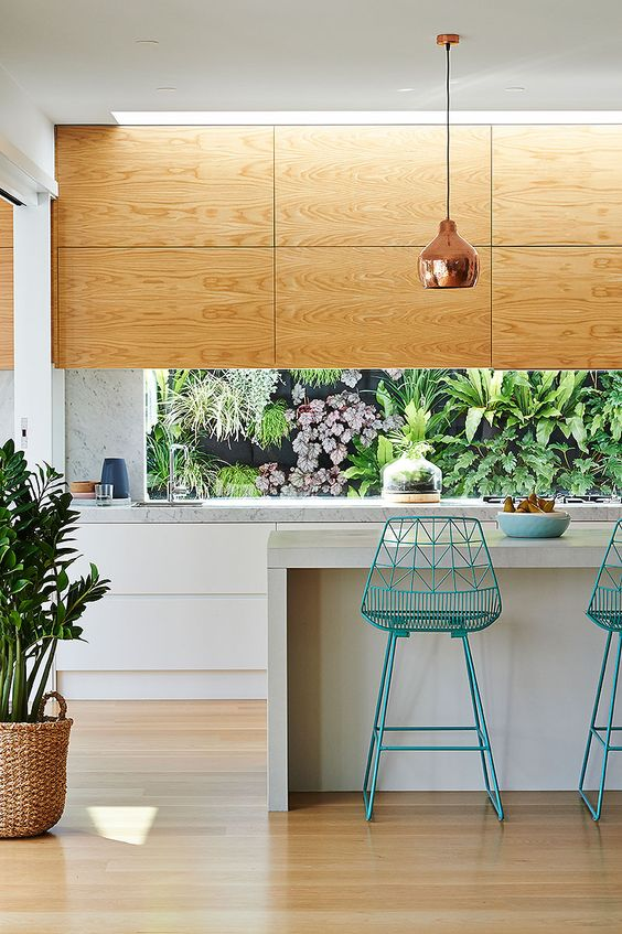 light-colored plywood and white cabinets plus stone counters look cool and modern and plants from outside refresh the kitchen