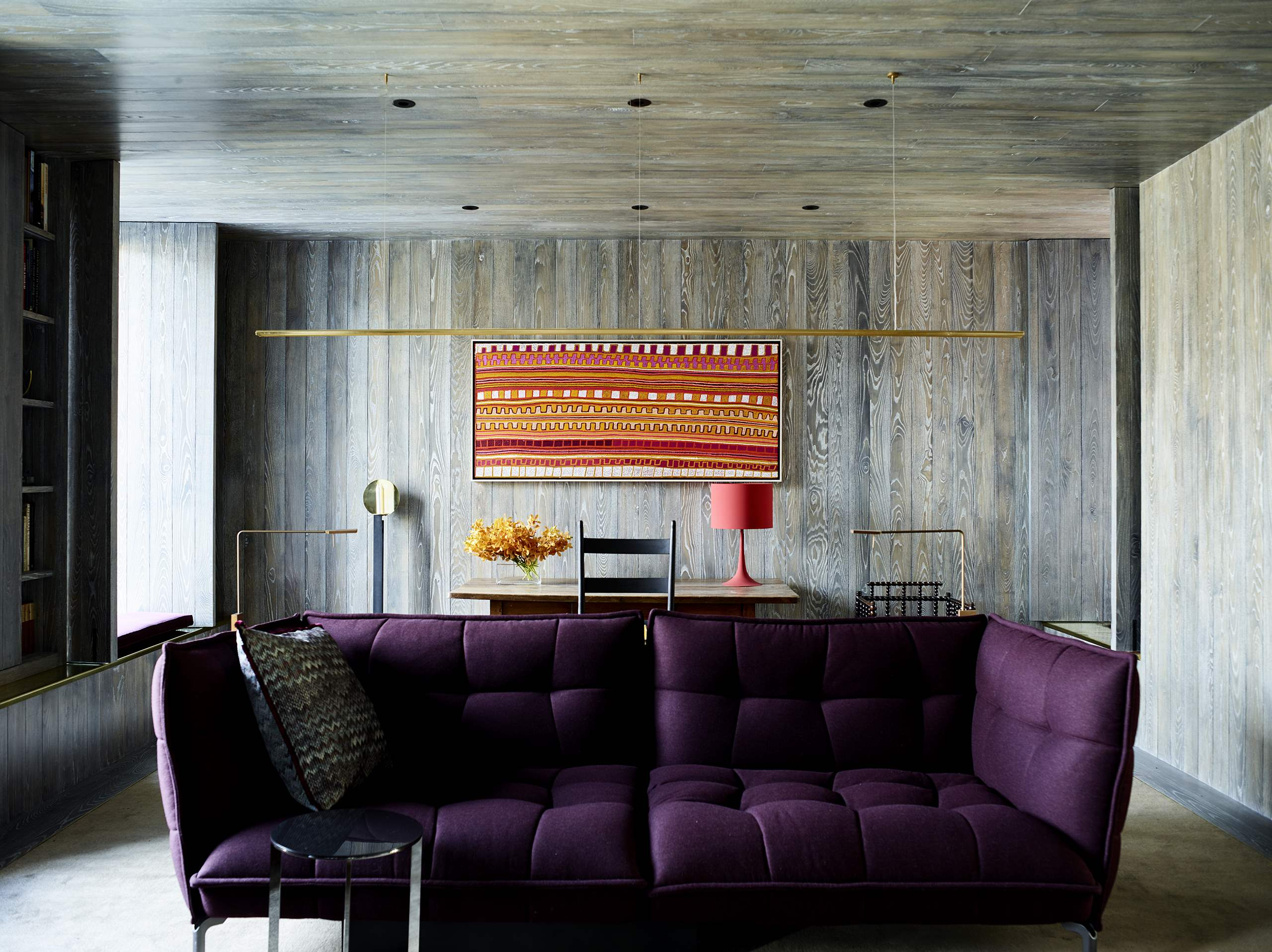 Here's another living room with an integrated workspace, almost fully clad with natural textural wood