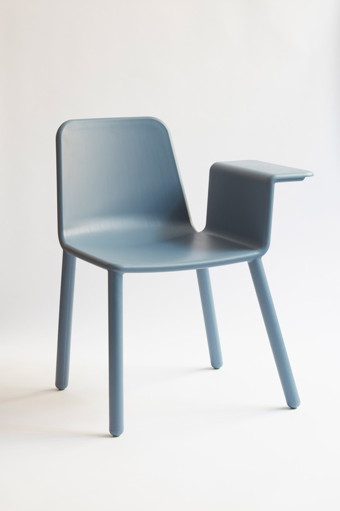 The chair features a side table attached to put a drink, an iPad or something else