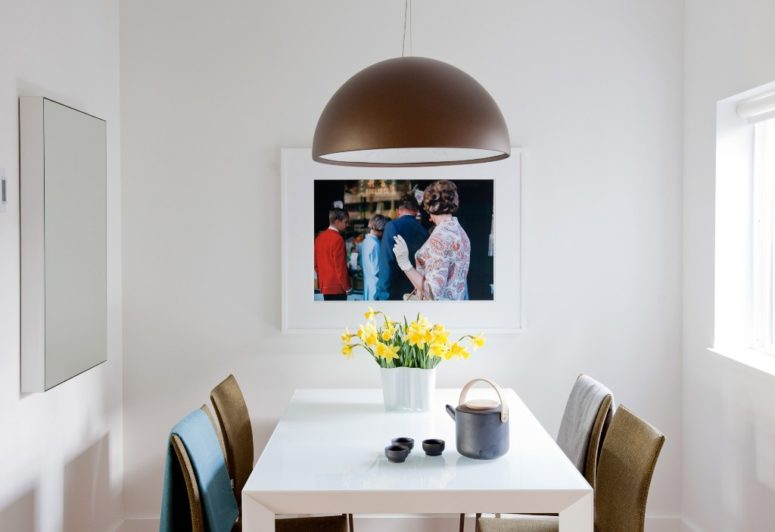 The dining zone features a comfy area for four people and an artwork plus a stylish pendant lamp
