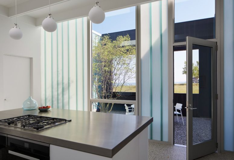 The kitchen is done with pendant lamps, cool views and sleek white cabinets, everywhere there's acess to outdoors