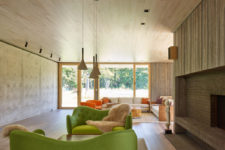 04 The living room is done with a large fireplace clad with brick and wood and a couple of bold green sofas