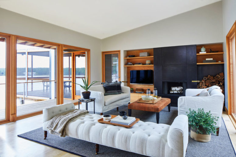 The living room is done with chic white upholstered furniture, wooden touches and is filled with light