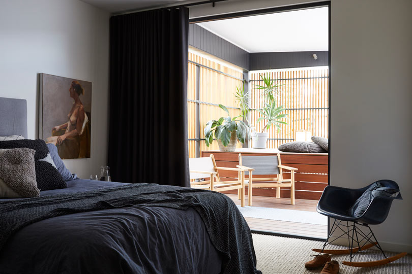 The master bedroom is moody for a relaxed feeling and there's access to the sunroom