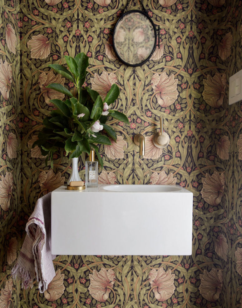The mudroom is done with bold printed wallpaper, a floating sink and a chic mirror
