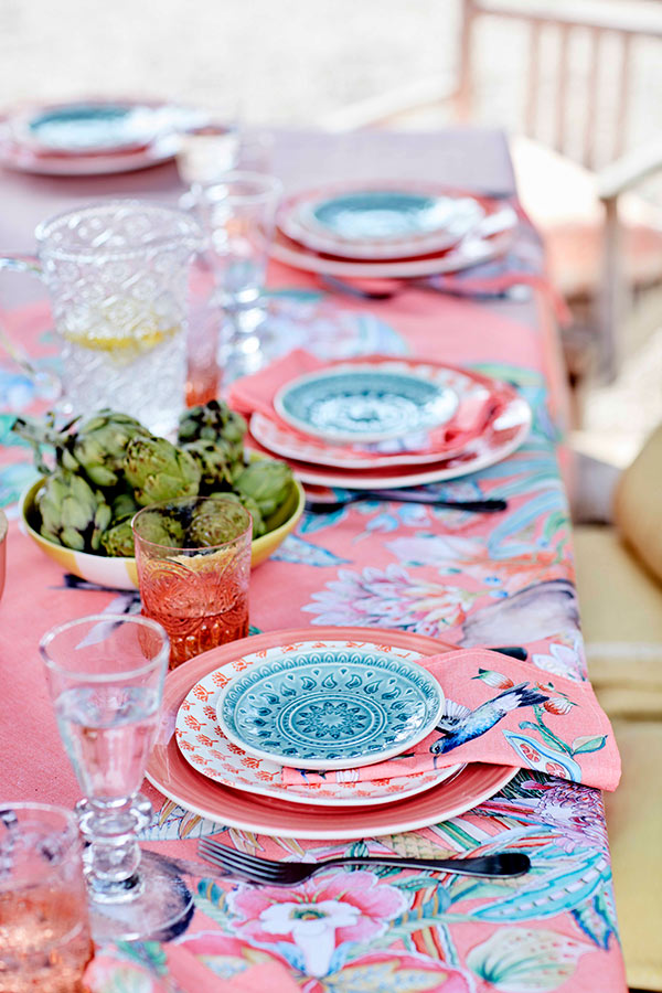 You may find coral pink tablecloths with floral prints, napkins with paradise birds and colorful plates