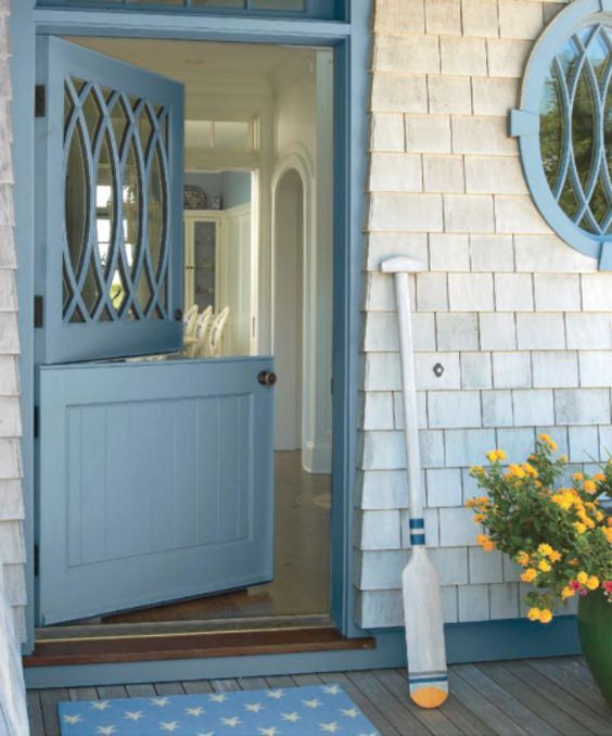 a blue Dutch door with a creative glass top part and shingles look cool together