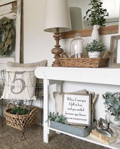 a farmhouse console table with a basket, much greenery in vases and some antique finds