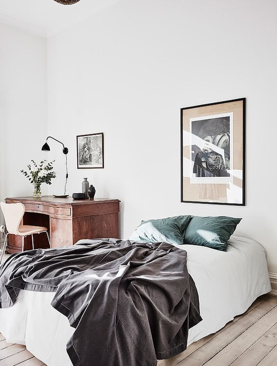 an airy and light bedroom with a bed and a vintage wooden desk in the corner