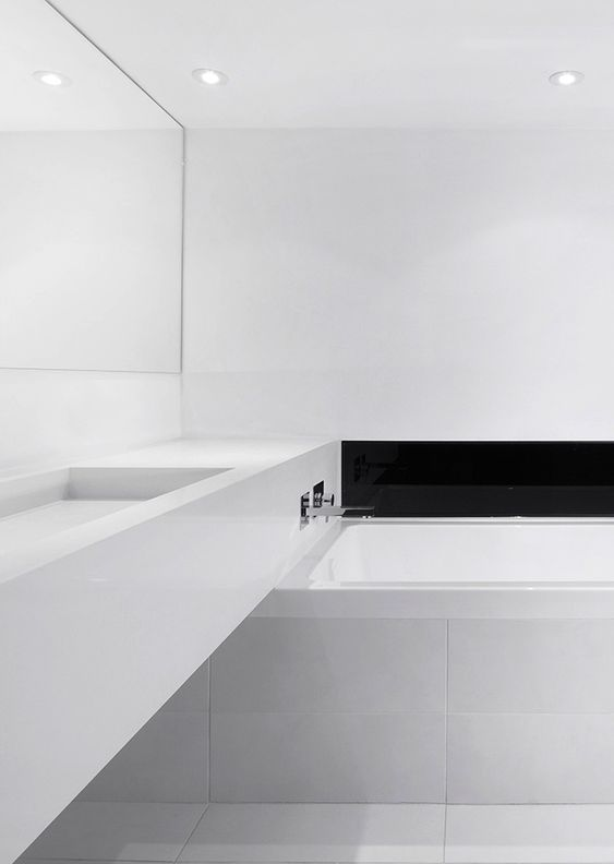 an ultra minimalist white bathroom with a black built in fireplace and a long vanity
