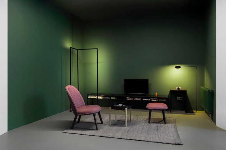 An irregular corner of the apartment has been put in the 'color pocket' in emerald with pink chairs