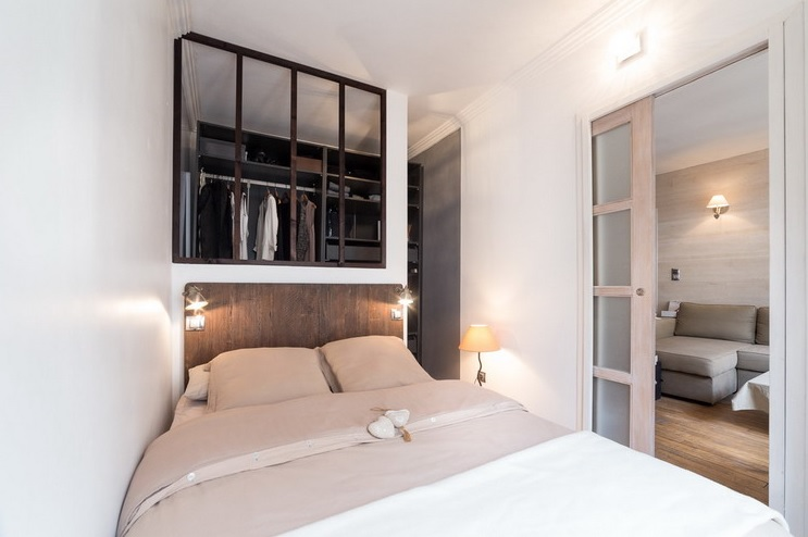 The bedroom is a tiny space with a large bed and sconces