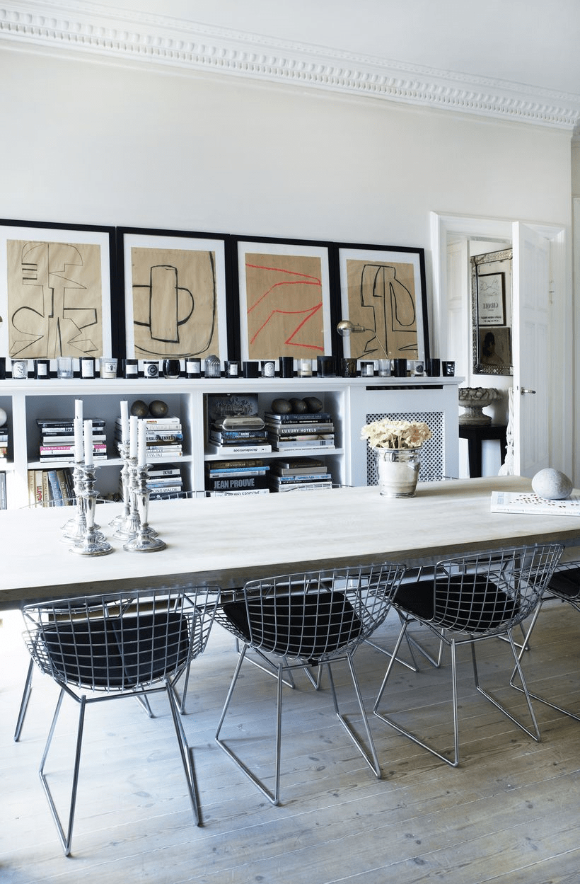 The dining room is done with a wooden table, metal chairs, a storage piece and a gallery wall
