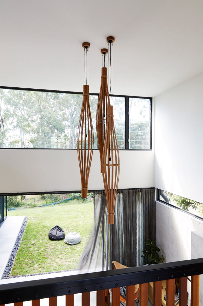 The double height ceiling is highlighted with long curved plywood lamps
