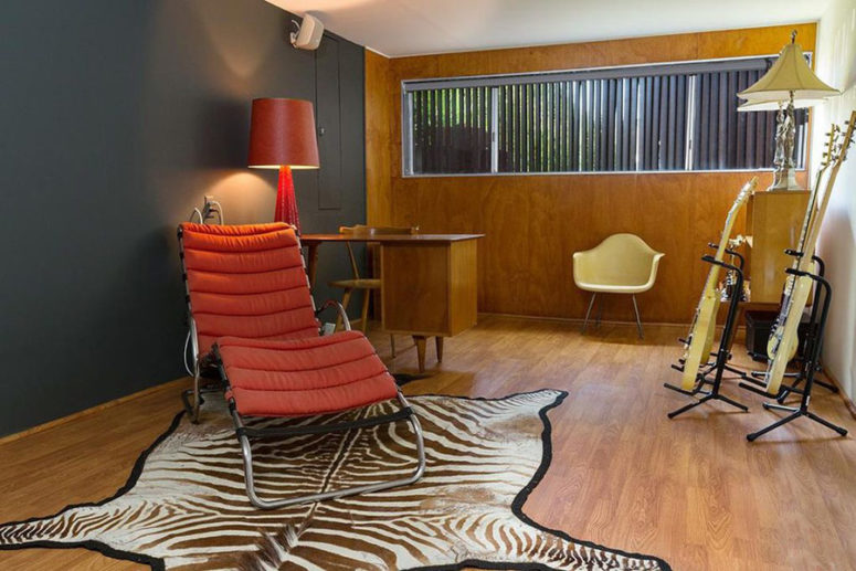 The home office is done in graphite grey and with plywood, with red touches and a faux zebra skin rug