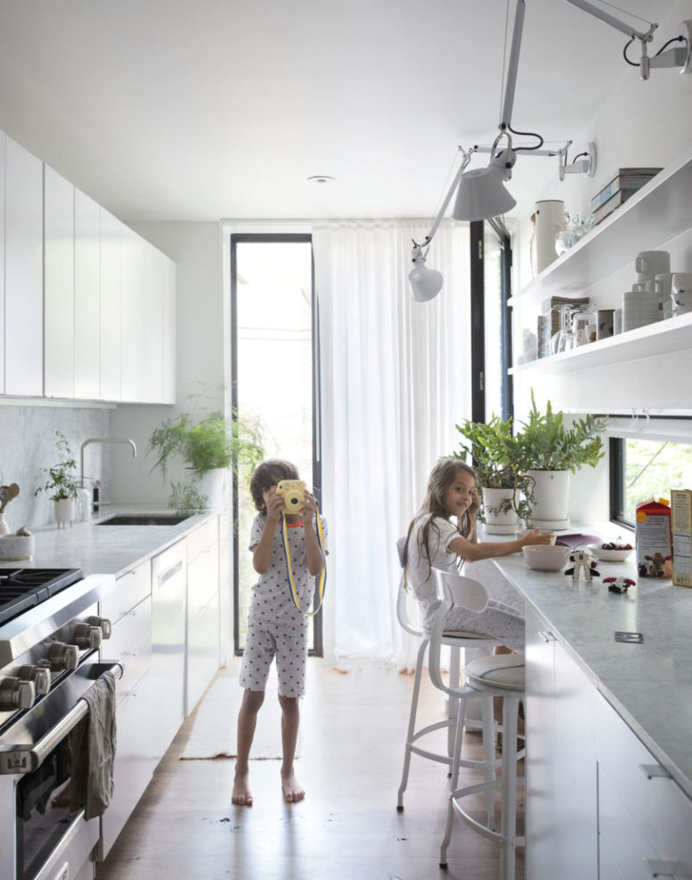 The kitchen is done with a tall narrow window, a window backsplash and comfy cabinets