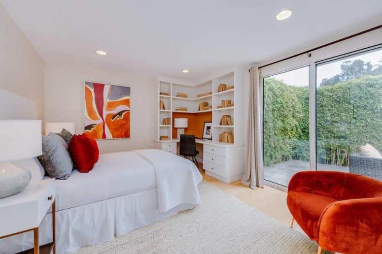 The second bedroom is accented with orange touches and looks very bright and shining