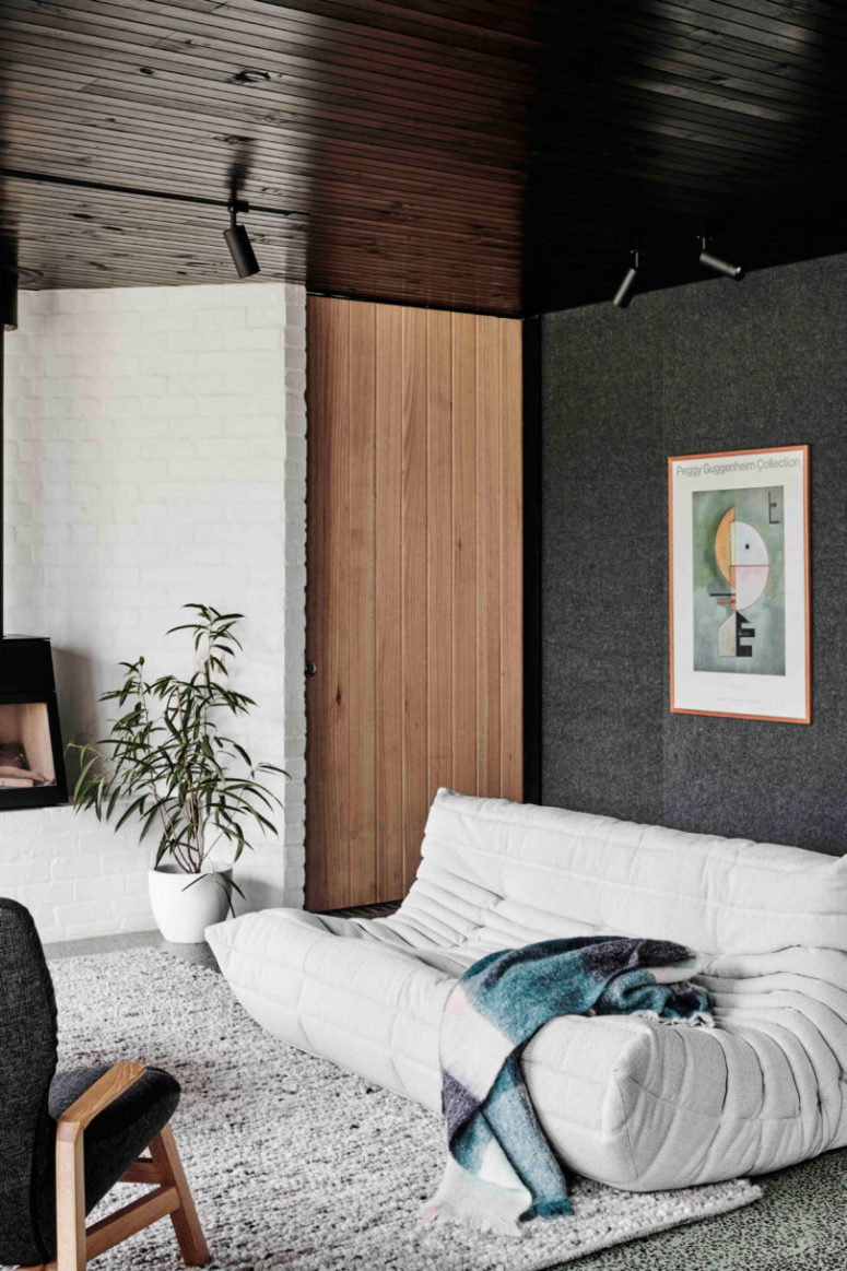 Touches of wood, a cool rug, greenery and an artwork make the space cooler
