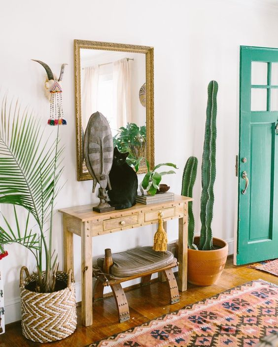 a boho summer console with a mask, greenery and a cactus around it and a cat on it
