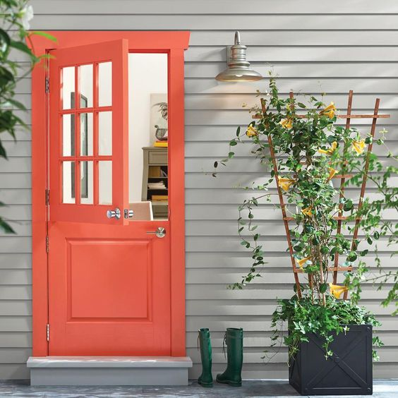a bright space with a red Dutch door, a planter with a trellis and green rubber boots for a rustic feel