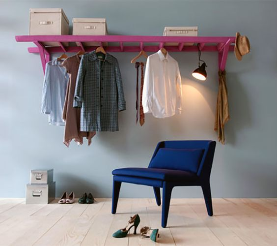 a fun and colorful wall-mounted shelf of a ladder painted pink for a modern and bold statement