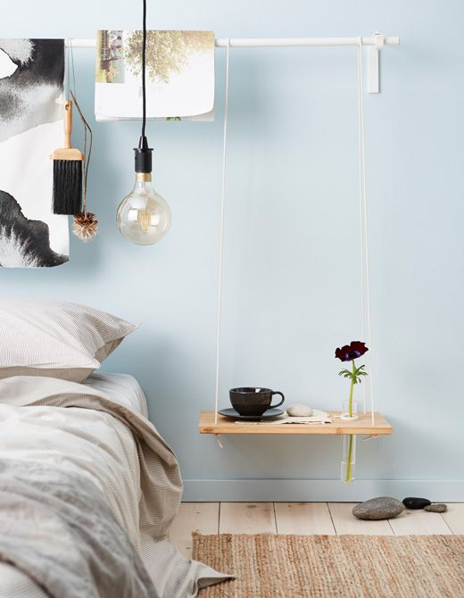 a low hanging bedside table styled as a swing of rope and a wood plaque for a contemporary space